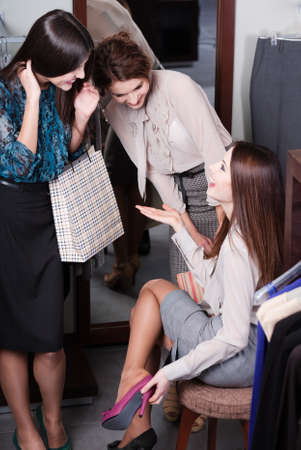 Women discuss bargains while trying on new fuchsia shoes photo