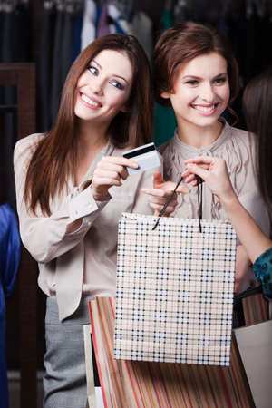 Pretty girls pay for purchases with credit card photo