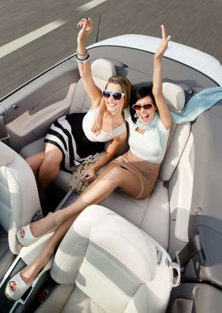 angle views: Top view of happy women in sunglasses with their hands up sit in the car Stock Photo