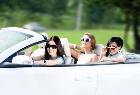 cabrio: Groep gelukkige tieners besturen van de cabriolet. Schattige autorit op vakantie Stockfoto