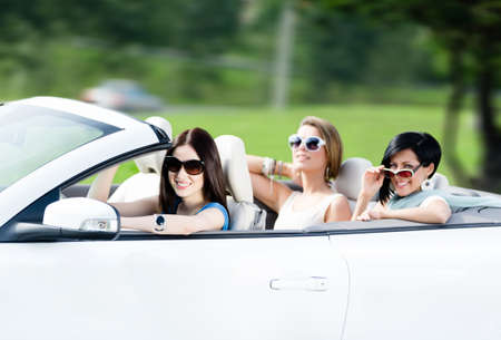 Group of happy teenagers driving the cabriolet. Adorable car trip on vacation photo
