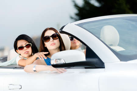 Girl showing something out of the convertible car to her driving friend photo