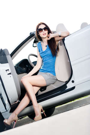 Pretty woman in sunglasses sits in the car with side door opened photo