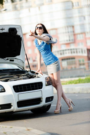 Woman thumbing a lift near the opened hood of the broken cabriolet and waiting for assistance photo