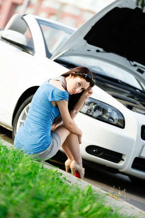 Woman sits on the grass near her broken car with the opened hood waiting for assistance photo