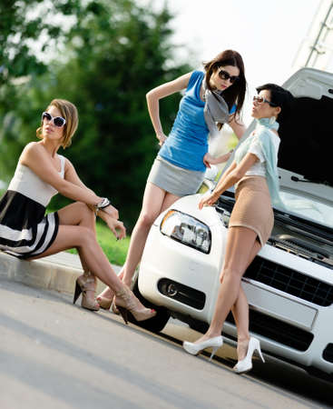 Group of three girls near the broken car with the opened hod waiting for help photo