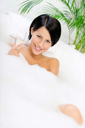 Woman taking a bath with suds drinks champagne and relaxes photo