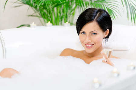 sexy bath: Woman taking a bath with suds and candles drinks alcohol and relaxes