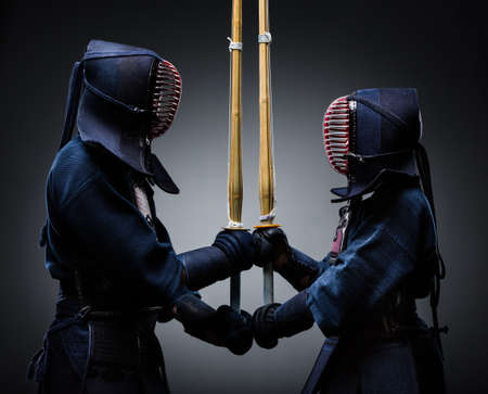 Two kendo fighters with shinai opposite each other Stock Photo