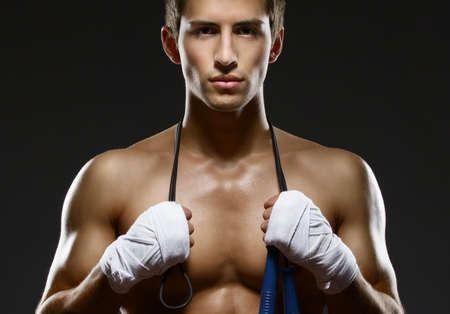 Portrait of sportsman keeping a string with his hands wrapped with elastic bandage photo
