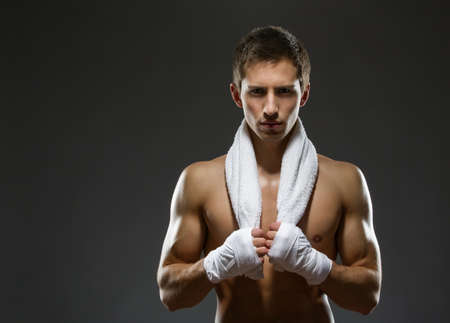 boxers: Portrait of fighter with white towel and his hands wrapped with protective bandage, isolated on black