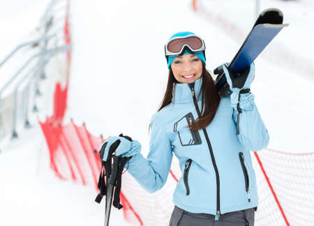 Half-length portrait of female wearing sports jacket and goggles who hands skis photo