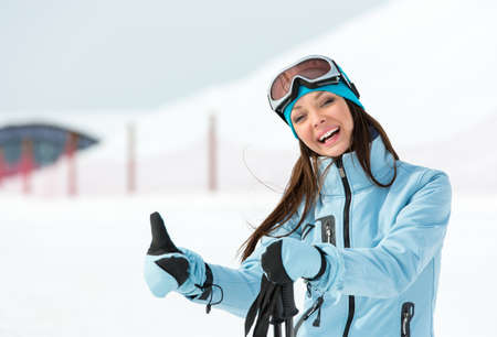 Half-length portrait of woman who goes skiing and wears goggles and sports jacket for winter sports photo