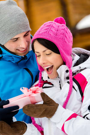 make a gift: Close up of man giving present to woman outdoors during winter holidays