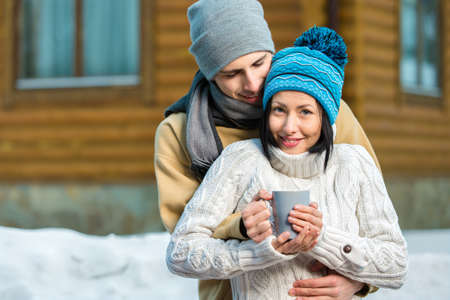 pullover: Half-length portrait of embracing couple drinking tea outdoors during winter vacations