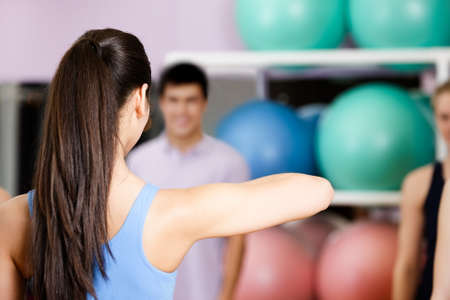 Young coach shows new exercises to the group of people at the gym in a fitness class photo