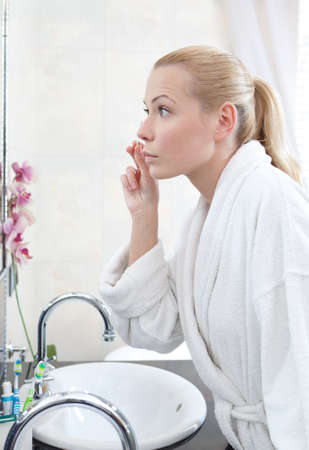 vertical format: Pretty woman washes face with lotion using wadding stick
