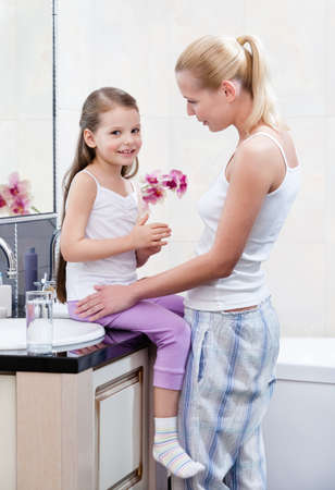 Mother and daughter talk about something in bathroom photo