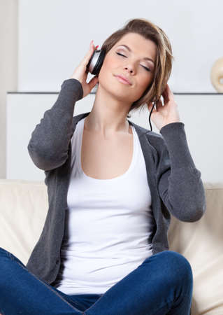 Sitting on the white leather sofa young girl in headphones listens to music photo