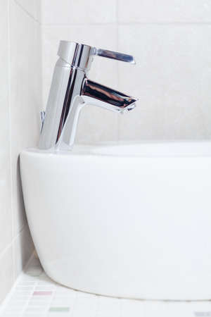 Side view of white basin with steel mixer faucet in bathroom photo