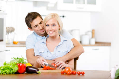 Young couple preparing breakfast sitting together at the breakfast table full of groceries photo