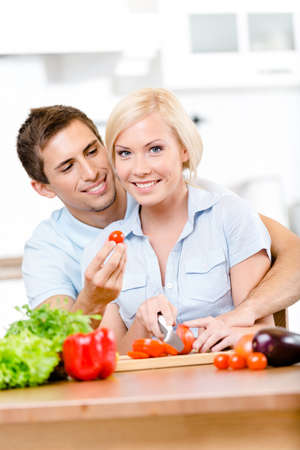 Married couple preparing breakfast sitting together at the breakfast table full of groceries Stock Photo - 22137244