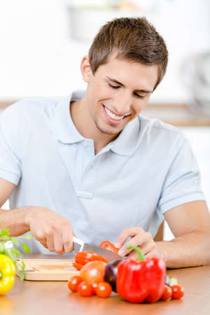 Man slicing groceries for breakfast while sitting at the kitchen table full of healthy food Stock Photo - 22137246