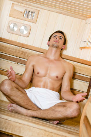 Half-nude woman relaxing in asana position in sauna  Concept of self-care, health and relaxation photo