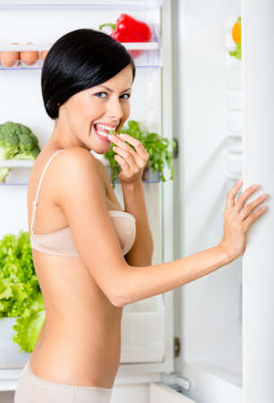 Young woman eating near the opened fridge full of vegetables and fruit  Concept of healthy and dieting food photo