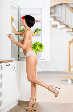 Full-length portrait of woman near the opened fridge full of vegetables and fruit  Concept of healthy and dieting food photo