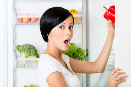 Young woman takes red pepper from the opened fridge full of vegetables and fruit  Concept of healthy and dieting food Stock Photo - 22137419