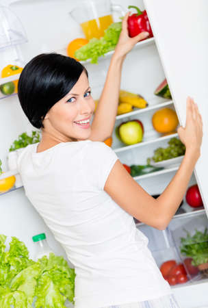 vertical fridge: Woman takes bell pepper from the opened refrigerator full of vegetables and fruit  Concept of healthy and dieting food Stock Photo