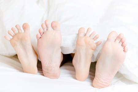 Nahaufnahme von zwei Paar Füße des Paares nebeneinander im Schlafzimmer