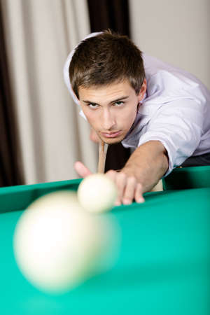 vertical format: Male playing billiards  Spending free time on gambling