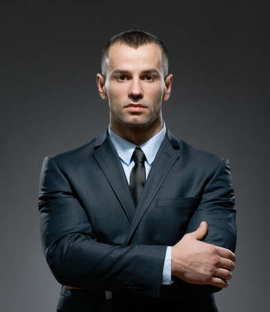 vertical format: Half-length portrait of businessman wearing business suit and black tie with arms crossed Stock Photo