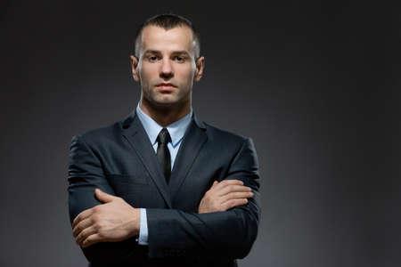 Half-length portret van man dragen pak en zwarte stropdas met gekruiste armen