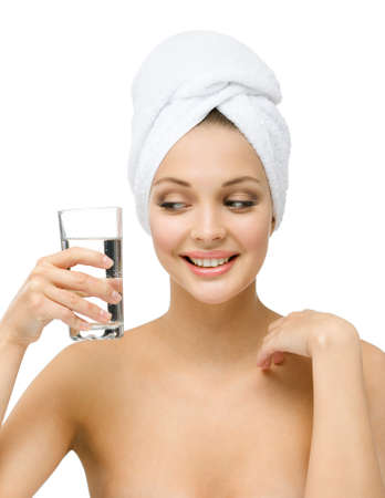 Girl with towel on head keeps glass of water, isolated on white  Concept of healthcare, beauty and youth photo