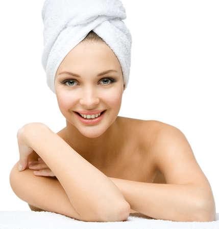 belle brunette: fille nue avec une serviette sur la tête touche son corps, isolé sur fond blanc Concept de la santé, de la beauté et de la jeunesse
