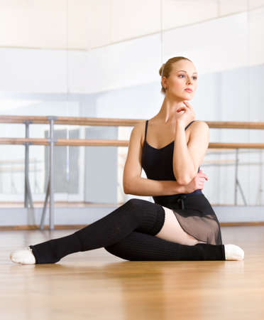 Ballet dancer does exercises sitting on the floor in the classroom with barre and mirrors photo