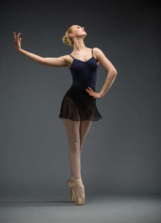 Full-length portrait of dancing ballerina with hand on hips, isolated on grey  Concept of elegant art and sportive hobby photo