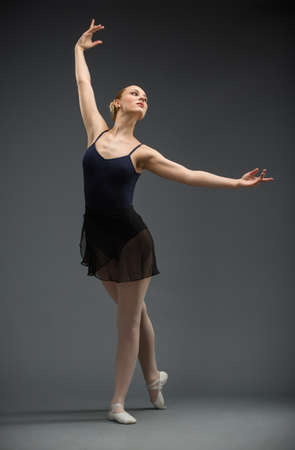 Full-length portrait of dancing ballerina with outstretched arms, isolated on grey  Concept of elegant art and sportive hobby photo