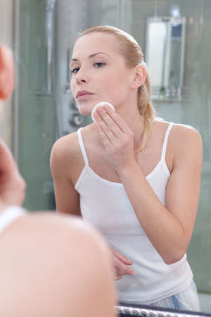 vertical format: Attractive woman washes face with makeup remover in bathroom