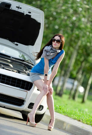 hair problem: Woman sitting on the hood of the broken car and waiting for assistance Stock Photo