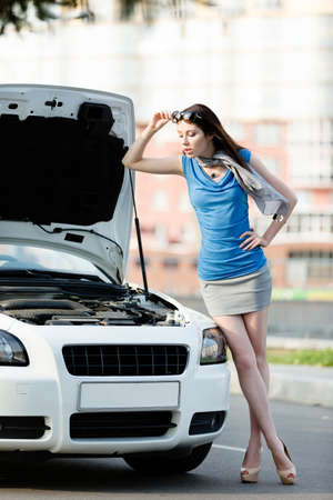 Woman repairing the broken car on the road. Girl stands near opened bonnet of the car after an accident