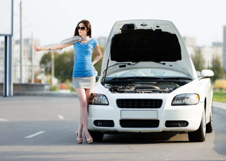 Woman hitchhiking near the opened hood of the broken car and waiting for assistance photo