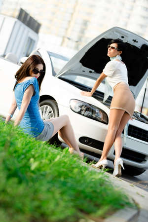 Two pretty girls try to repair the broken car on the road photo