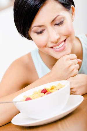 Close up view of girl near the plate with muesli and strawberry photo