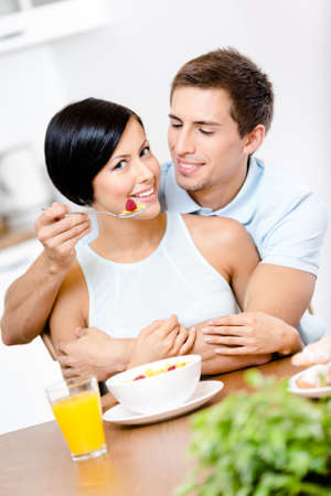 Man feeds and embraces his girlfriend sitting at the kitchen table. Concept of tasty and dieting food photo