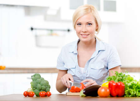 Woman cuts vegetables for salad sitting at the kitchen table Stock Photo - 22279301