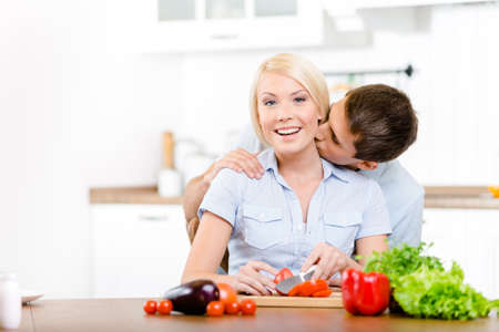 Man kisses girl while she is cooking sitting at the kitchen table full of vegetables photo